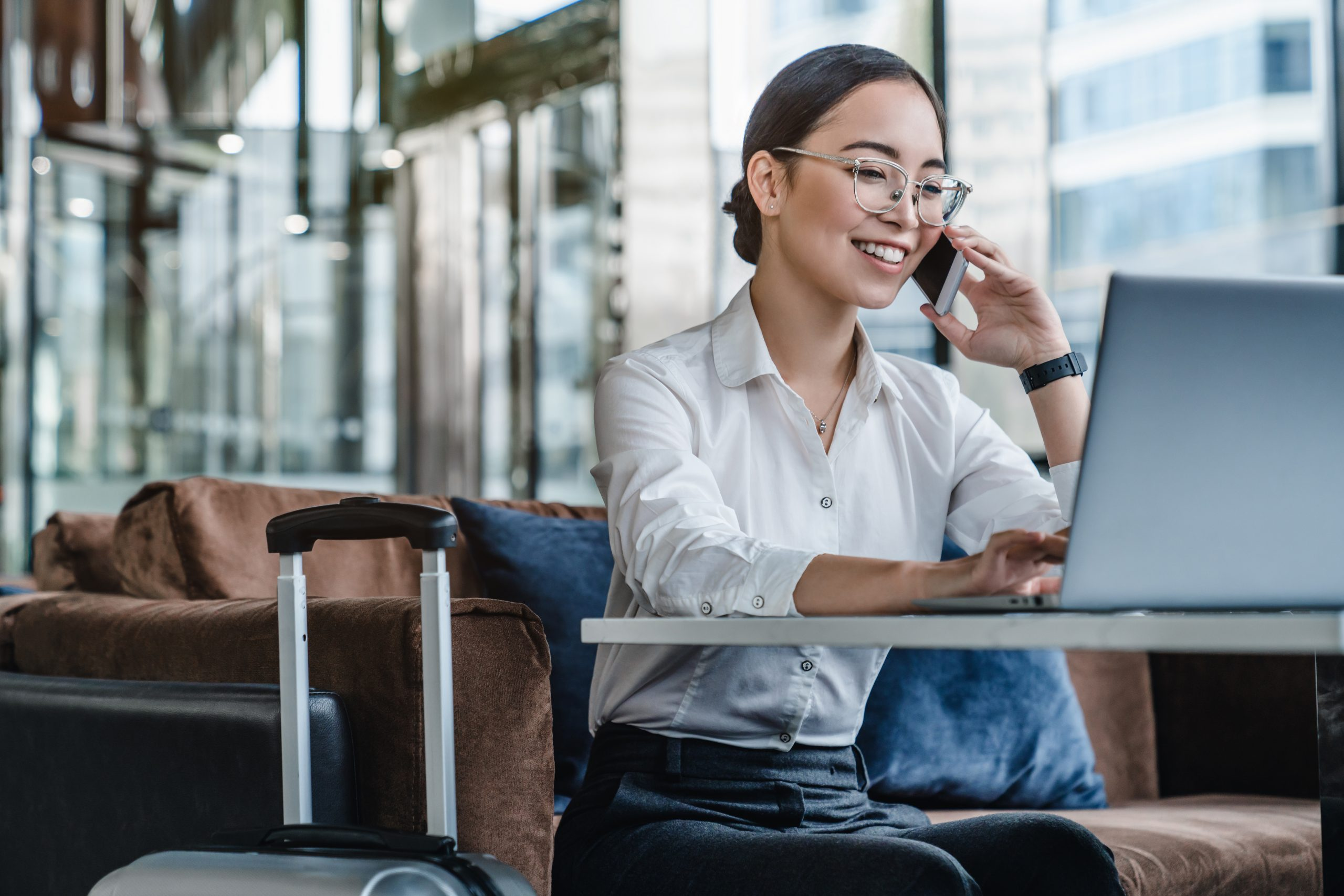 Asian female sitting at airport before trip having telephonic conversation with client and smiling.